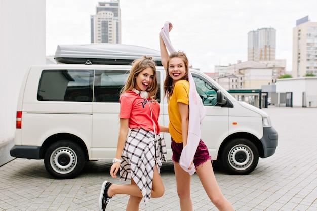 밝고 트렌디 한 옷을 입은 세련된 소녀들이 미소를 지으며 춤을 추고 함께 야외에서 놀아요.
