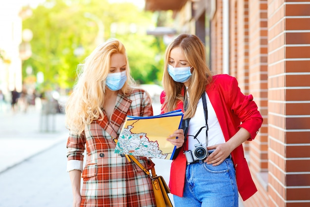 Stylish girls looking into tourist map in the city