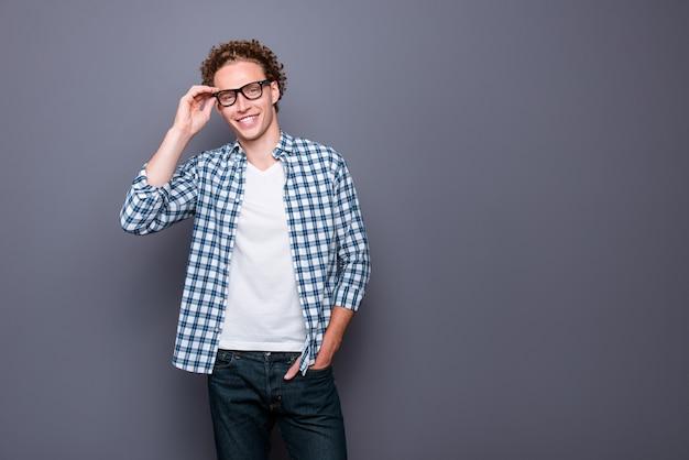 メガネに触れるカジュアルな市松模様のシャツのスタイリッシュな嬉しい若い男