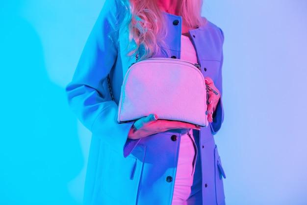 スタジオでカラフルなネオンピンクの光に青いジャケットを着たファッショナブルな革のハンドバッグを持つスタイリッシュな魅力的な女性。女の子は白い流行のバッグを持っています