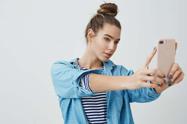 Stylish glamour young woman taking selfie, posing sassy flirty looking display smartphone, holding mobile phone making assertive facial expression