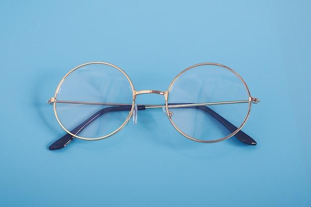 青色の背景にスタイリッシュなゴールドのメガネ