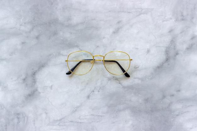 Stylish gold eyeglasses spectacles on marble background. minimal style