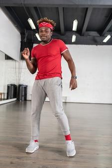 スポーツホールで移動しながら赤と灰色の服を着てスタイリッシュな格好良いダンサー