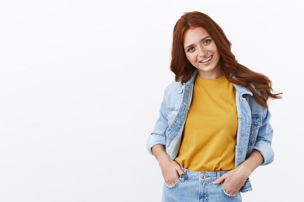 デニムジャケットに赤い巻き毛の髪型をしたスタイリッシュでかっこいいヨーロッパの女の子、ポケットに手をつないで、頭を傾けて陽気に笑い、自信を持って野心的に立って、活気のあるパーティー、スモールトークをお楽しみください