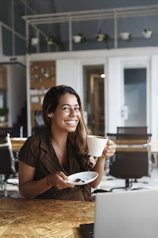 Stylish good-looking office lady enjoying hot coffee holding cup sitttin in cafe alone