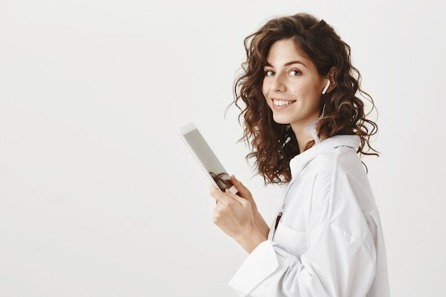 Elegante splendida imprenditrice in auricolari wireless con tavoletta digitale