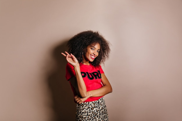 Stylish gorgeous woman in t-shirt standing in studio and laughing
