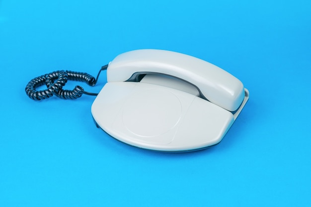 青の背景にスタイリッシュな灰色のレトロな電話。レトロなコミュニケーション手段。