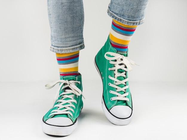 Стильные зеленые кроссовки и забавные носки на белой стене. понятие моды, красоты и хорошего настроения