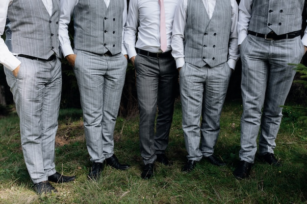 Stylish groom and his groomsmen stand on grass