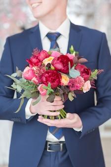 結婚式の花束を保持しているスタイリッシュな新郎