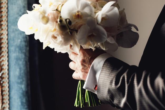 Stylish groom holding amazing bouquet of roses