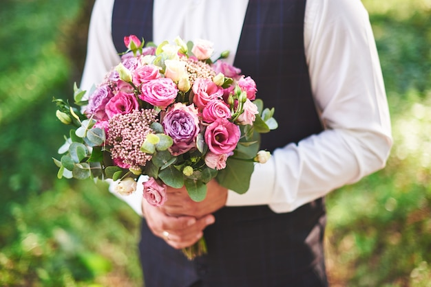 Stylish groom holding a tender pink wedding bouquet.