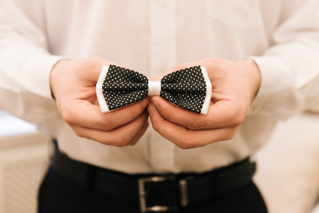 Stylish groom putting on suit and bow tie. confident and happy portrait of man. groom getting ready in morning. creative wedding photo
