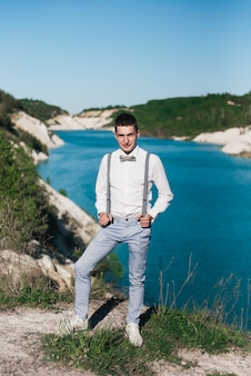 Stylish groom in a white shirt, blue pants, bow tie and suspenders