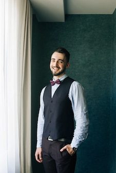 Stylish groom in white shirt and bow tie posing at window light