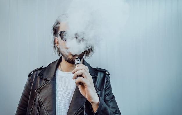 Stylish guy in a black leather jacket smoking a vape