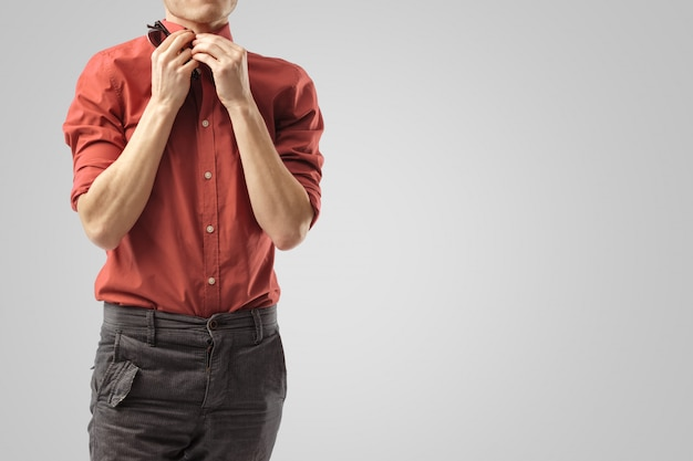 スタイリッシュな男は彼のシャツを締めます。