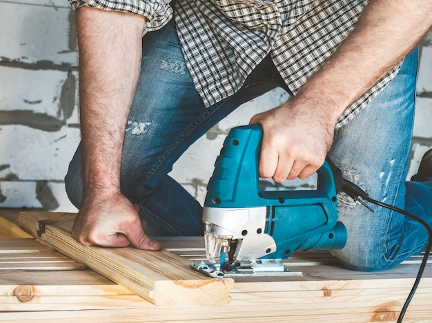 야구 모자, 청바지와 셔츠를 입은 세련된 남자가 건설중인 집안의 나무에 도구를 사용합니다. 건설 및 수리의 개념