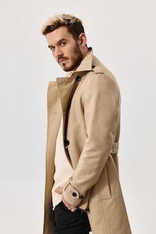明るい背景の肖像画のクローズアップの髪型モデルのジャケットのスタイリッシュな男