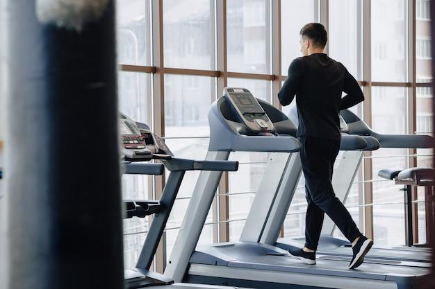 Стильный парень в тренажерном зале занимается на беговой дорожке. здоровый образ жизни.