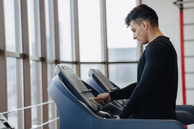 ジムでスタイリッシュな男がトレッドミルでトレーニングしています。健康的な生活様式。