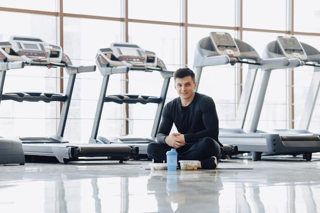 Стильный парень в тренажерном зале, отдыхая на полу и едят здоровую пищу.