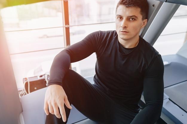 Стильный парень в тренажерном зале сидит отдыхая на беговой дорожке. здоровый образ жизни.