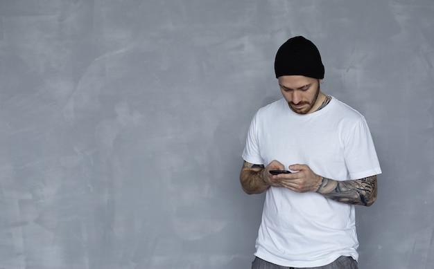 白いtシャツと携帯電話で黒い帽子のスタイリッシュな男