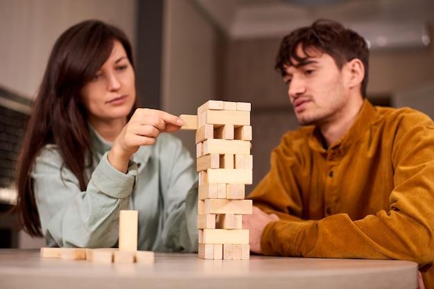 Стильный парень строит башню с подругой дома и проводит выходные вместе
