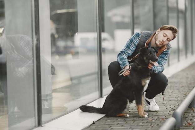 Стильный парень играет с собакой. человек в осеннем городе.