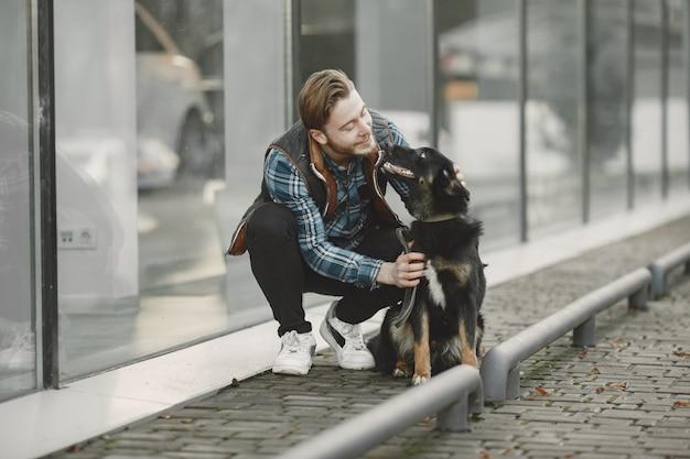 Ragazzo alla moda che gioca con un cane. uomo in città d'autunno.