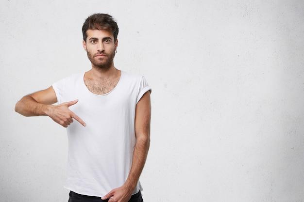 그의 빈 빈 흰색 티셔츠를 가리키는 세련 된 남자