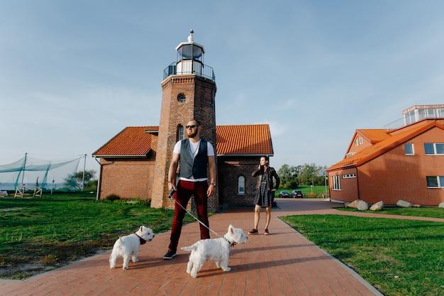 Стильный парень, стоящий на улице держателя на поводке двух маленьких белых собак