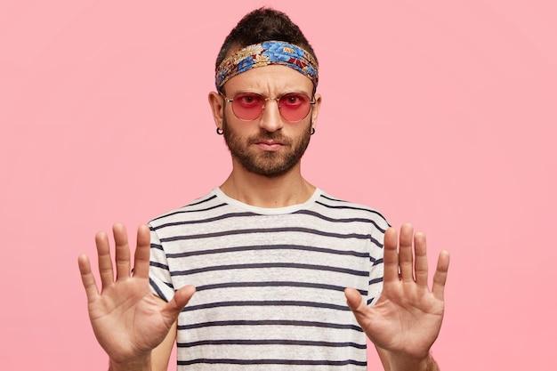 Ragazzo alla moda che indossa occhiali da sole e fascia colorata