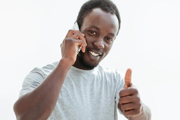 Стильный парень со смартфоном показывает палец вверх