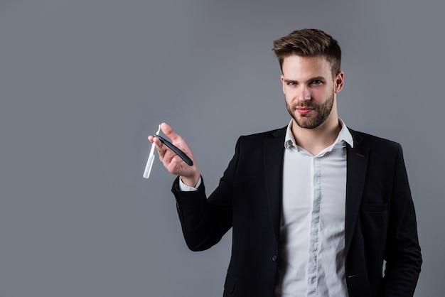 トレンディな髪型のスタイリッシュな男は、オフィススーツを着て、かみそりの刃、理髪店を保持します。