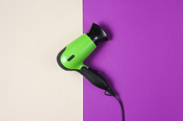Stylish hair dryer on purple-beige. top view.