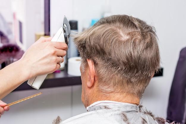 美容院で老人のためのスタイリッシュなヘアスタイリング