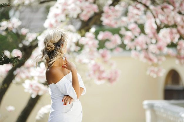 Stylish hairdo of blonde in white dress