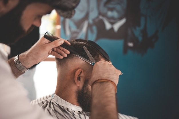 Stylish hairdresser in a cap does a haircut