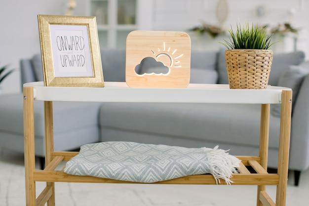 회색 소파가있는 거실 내부의 세련된 손으로 만든 가정 장식. 사진 프레임, 태양과 구름 그림이있는 장식용 나무 램프, 고리 버들 꽃 냄비에 녹색 식물이있는 트렌디 한 커피 테이블.