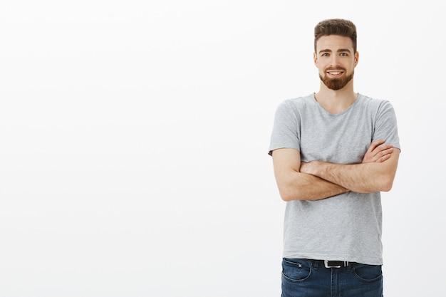 세련된 잘 생기고 자신감 넘치는 창조적 인 사업가 가슴에 팔을 교차하고 회색 벽 위에 야심 차고 기쁘게 서있는 모든 기술에 자신감을 가지고 친절하고 기뻐 웃는 느낌