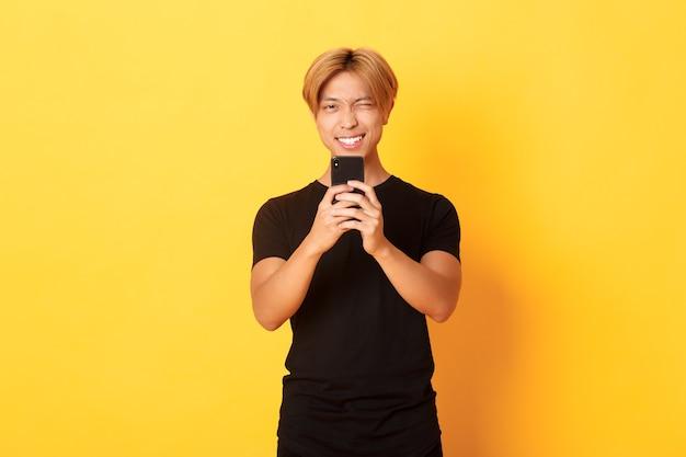 スタイリッシュなハンサムなアジア人の男がスマートフォンで写真を撮って、笑みを浮かべて、携帯電話で写真を撮って、黄色の壁に立っています。