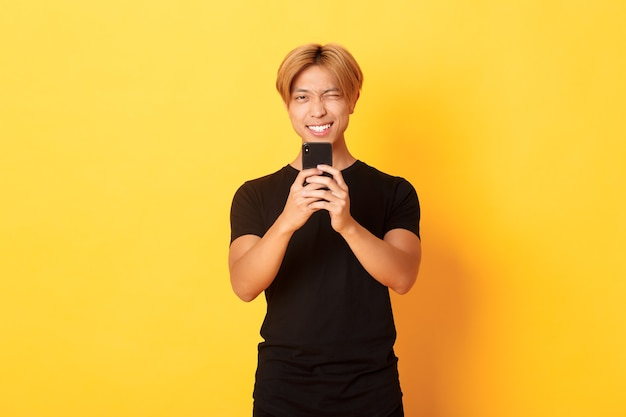 Stylish handsome asian guy taking picture on smartphone and smiling, photographing with mobile phone, standing yellow wall