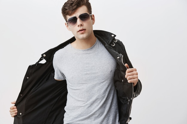 Stylish handsome attractive european young man with trendy haircut dressed in trendy black leather jacket, wearing sunglasses. caucasian male model posing indoors .