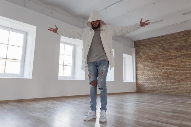 벽돌 벽이있는 흰색 방에서 포즈를 취하는 흰색 운동화와 함께 찢어진 청바지에 후드가 달린 재킷에 세련된 잘 생긴 매력적인 모델 남자