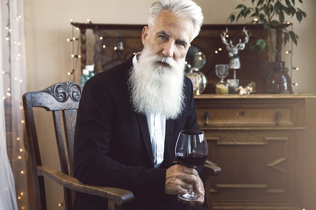 Stylish and handsome bearded senior man drinking red wine