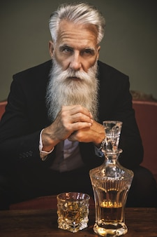 Stylish and handsome bearded senior man drinking whiskey